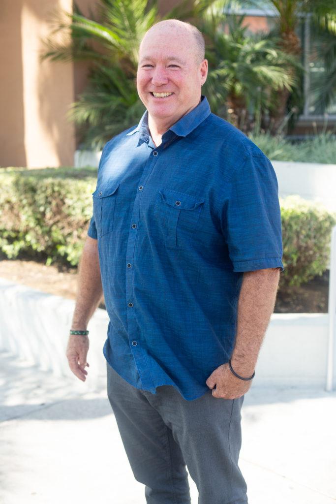 Más viejo hombre blanco vestido con camisa azul marino de manga corta y pantalones grises