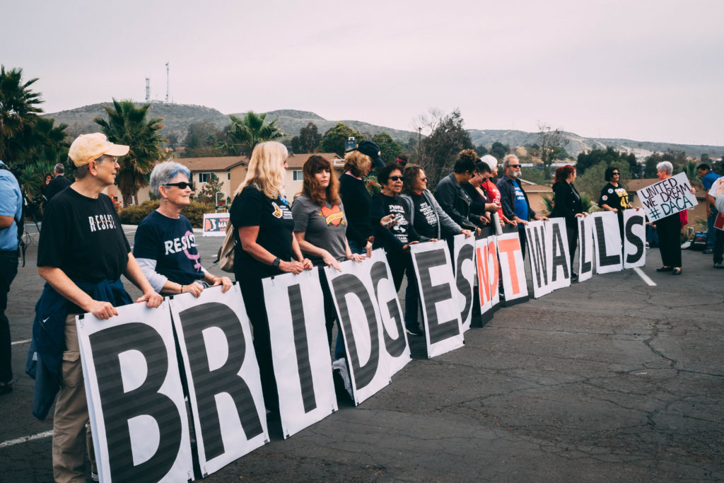 Group of people during rally holding letters that read bridges not walls