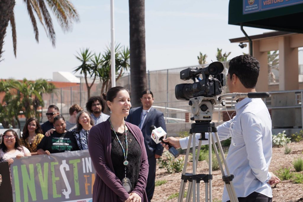 Young caucasian woman speaking to television camera during interview