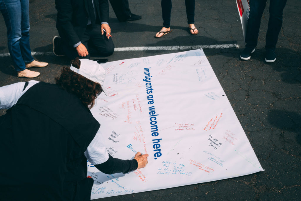 Woman signing an Immigrants Are Welcome Here poster