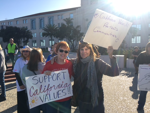 Two woman holding protest signs in support of California Values Act