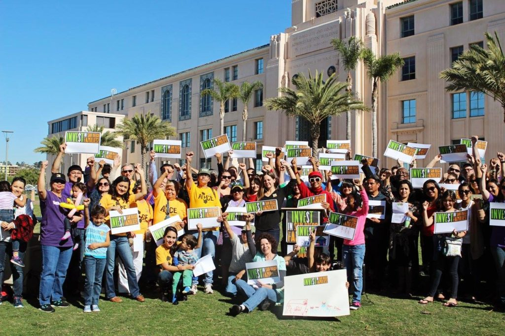 Group of people from different ethnic backgrounds holding up signs that read invest in San Diego families