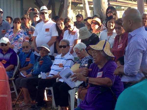 Older asian woman speaking to a group of people during save PQ Village rally