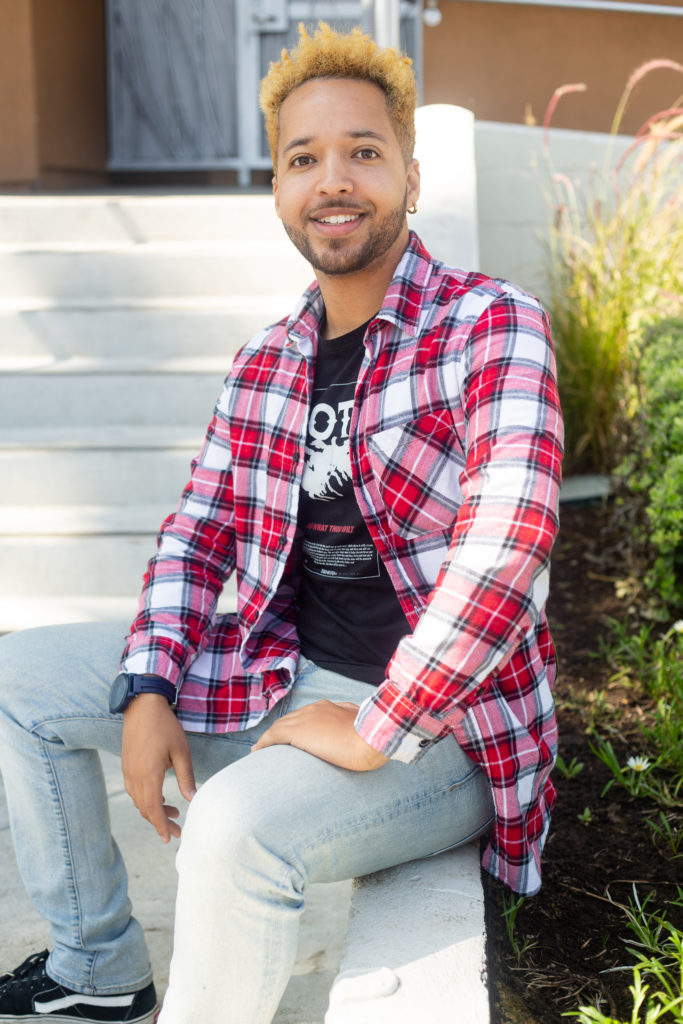 Young man with dyed blonde hair sitting outside of building wearing quilted unbuttoned shirt, black t-shirt, light blue jeans, and black sneakers