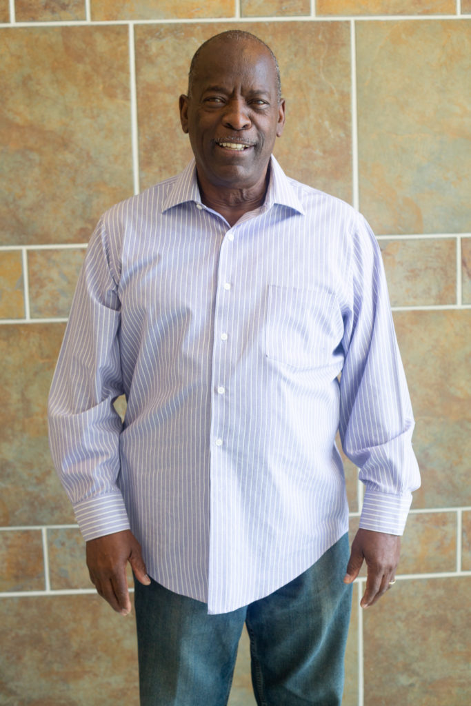 Older black man wearing a lavender colored shirt and jeans