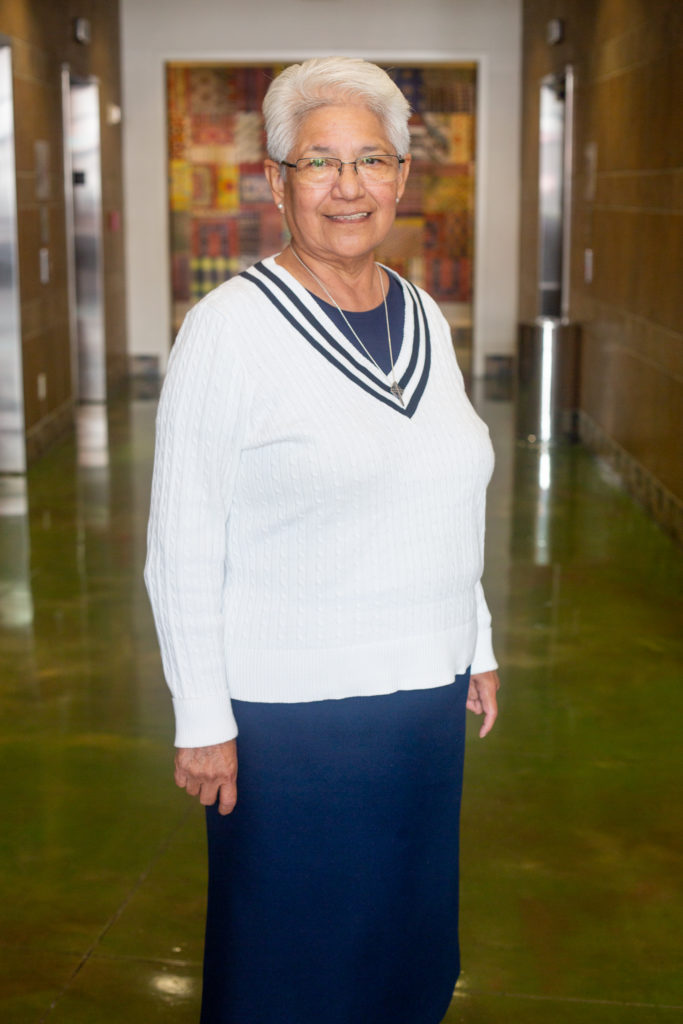 Older woman standing on a hallway wearing a white sweater and blue dress