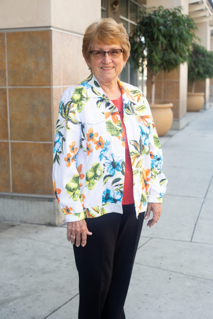 Older woman with short blonde hair standing outside of building wearing a white jacket with flowers, red blouse and black pants