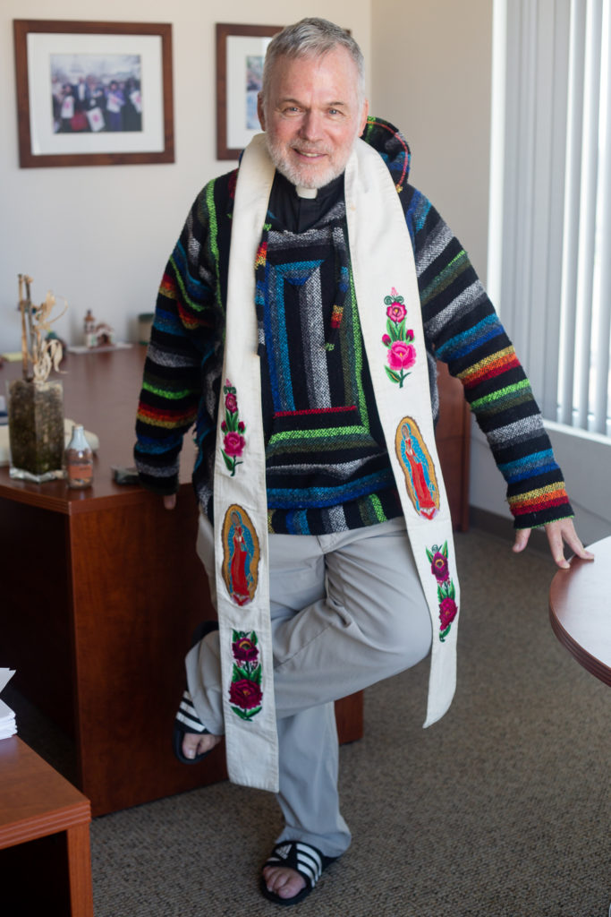 A priest wearing a Virgin Mary Stole and a traditional colorful mexican hoodie