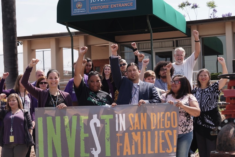 Multiple people from different ethnic backgrounds holding up their fist in support of San Diego families
